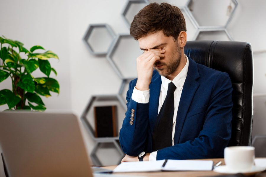Upset young businessman in suit sitting at workplace, wiping eyes, office background.