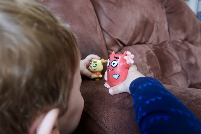A child playing with 2 plastic figurines