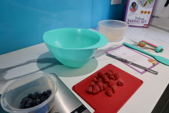A baking set up, with berries, a mixing bowl and a recipe