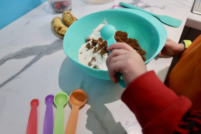 A mixing bowl with flour and sugar in it, with a childs hand tipping in a measuring spoon