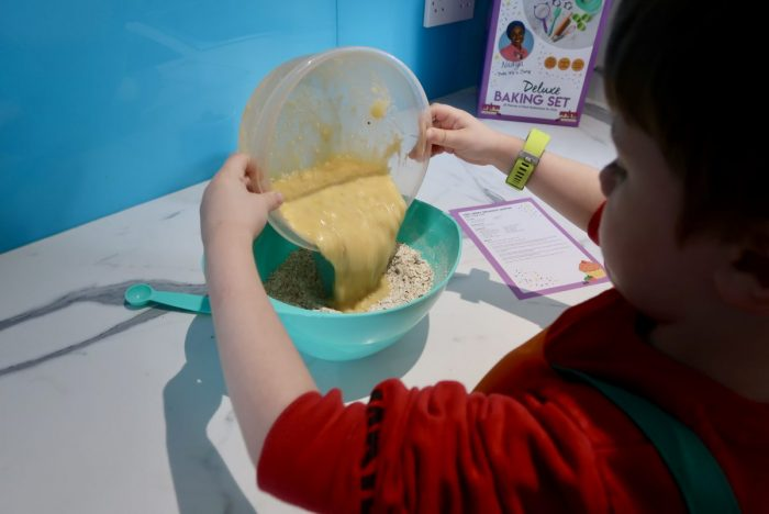 A child pouring wet mixture into a bowl of flour
