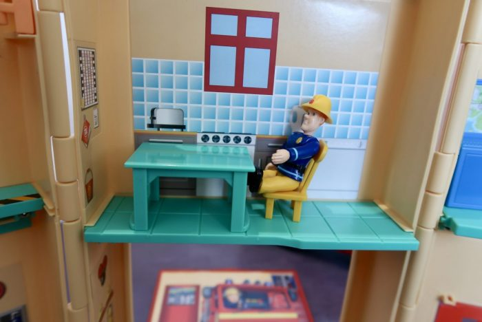 Fireman Sam sitting at a table in the kitchen