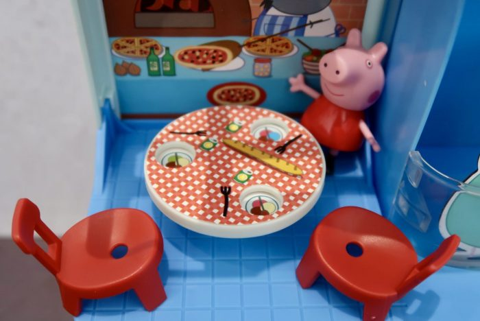 Peppa Pig standing next to a table with ice cream on the plates