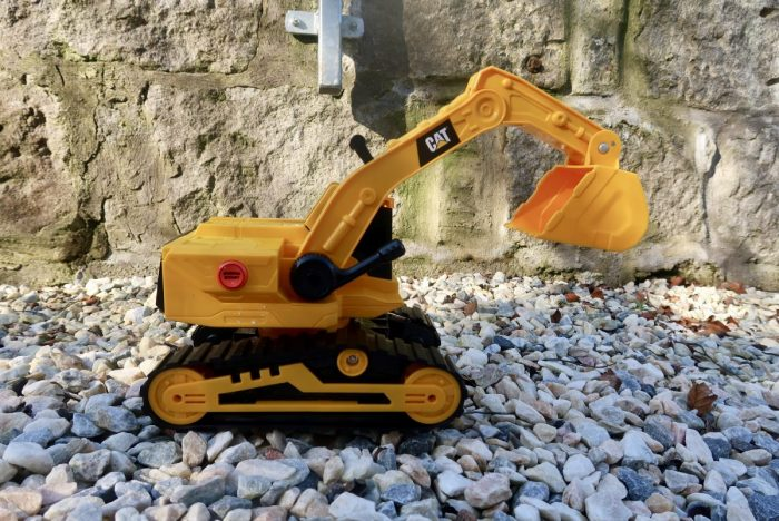 A toy digger sitting on some stones