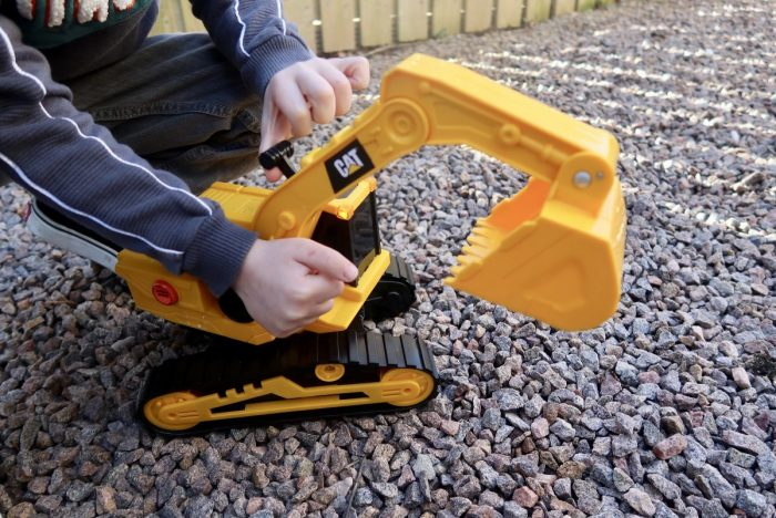 A yellow toy digger being moved by a childs hands