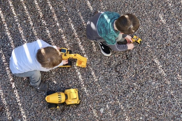 A top down view of children playing with yellow construction vehicle toys