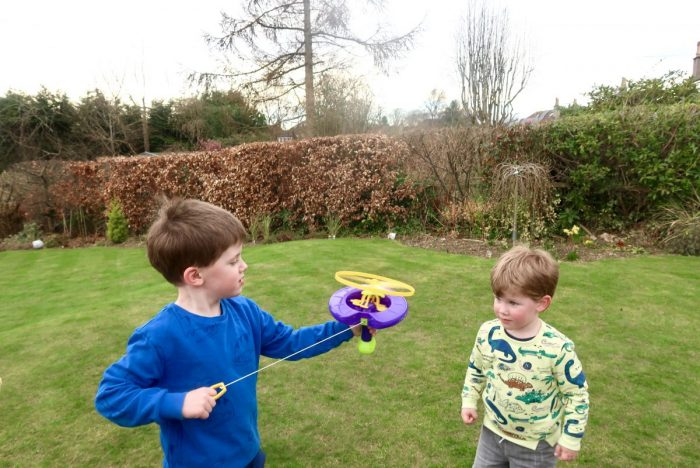 2 children in the garden. One is holding a helicopter bubble toy and pulling the string