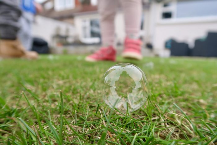 A bubble sitting on grass with childrens legs behind it