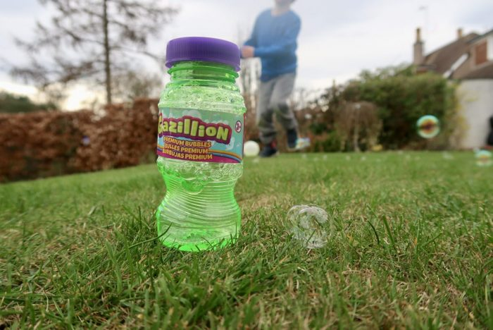 A bottle of bubble mixture on the grass next to a bubble, with a child playing in the background