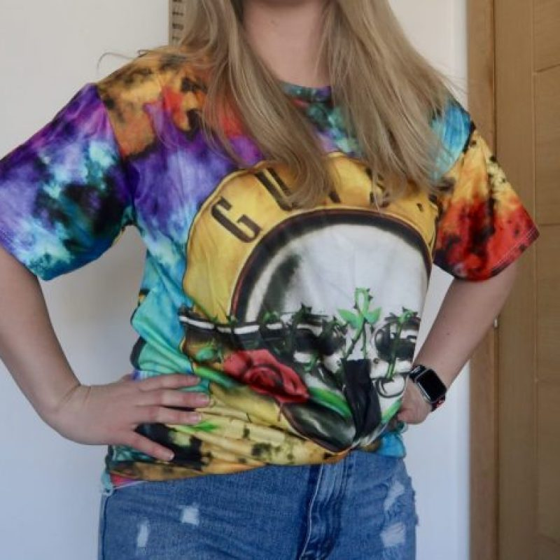 A woman with her hands on her hips, wearing a tie-dye t-shirt
