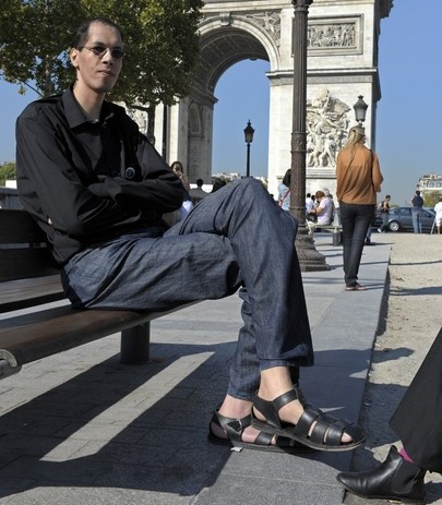 Morocco's Brahim Takioullah, who has the largest feet of the world according to the Guinness Book of Records, poses in front of the Arc de Triomphe on the Champs-Elysees on September 29, 2011 in Paris. Takioullah's left foot measures 38.1 cm (1 ft 3 in) while his right foot measures 37.5 cm (1 ft 2.76 in). At right a woman shows her foot to make a comparison.      AFP PHOTO BERTRAND GUAY (Photo credit should read BERTRAND GUAY/AFP/Getty Images)