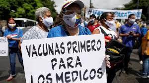 """Una mujer con una mascarilla sostiene una pancarta que dice """"¡Las vacunas para los médicos primero!"""" durante una protesta para exigir vacunas contra el COVID-19 para todas las personas, en Caracas (Reuters)"""