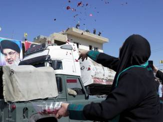 A woman tossing flower petals and rice at the convoy in a village in northeastern Lebanon. Credit: Issam Abdallah / Reuters