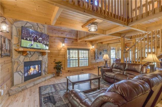 A great room indeed - The living area of the main floor�??s great room includes comfortable leather couches, a stone-surround fireplace, and 65�?� smart HDTV.