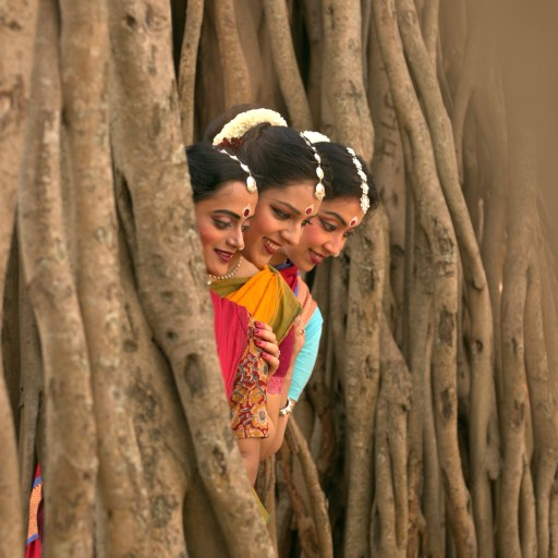 Three dancers looking from a Banyan tree
