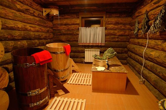 Интерьер бани из бревна, деревянные бочки, веники