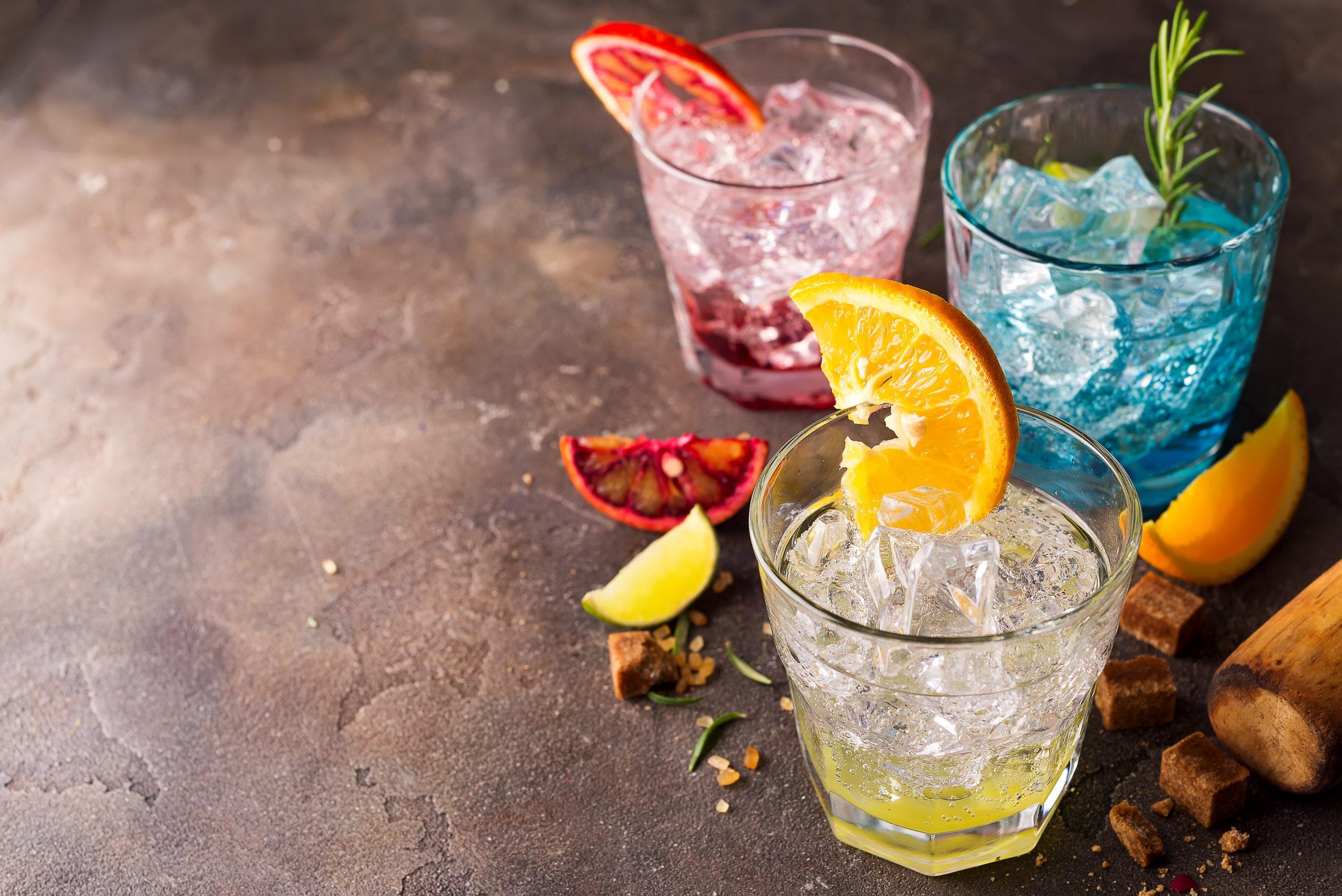 Kolorowe drinki w szklankach, udekorowane owocami i ziołami