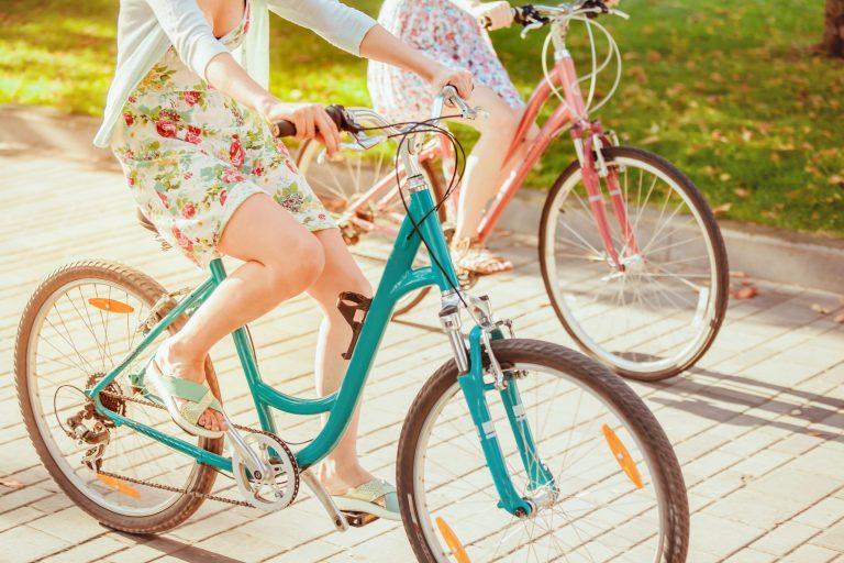 Dwie kobiety jadące na rowerach przez park