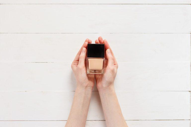 Jak dobrac podkład do rodzaju cery? Kobieta trzma w dłoniach fluid do makijażu