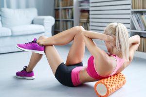 Kobieta wykonuje ćwieczenia fitness przy pomocy wałka (roller exercise)