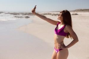 Jak zadbać o telefon w upalne dni. Młoda kobieta robi selfie na plaży