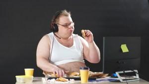 Mężczyzna z nadwagą objada się podczas pracy przed komputerem w czasie kwarantanny