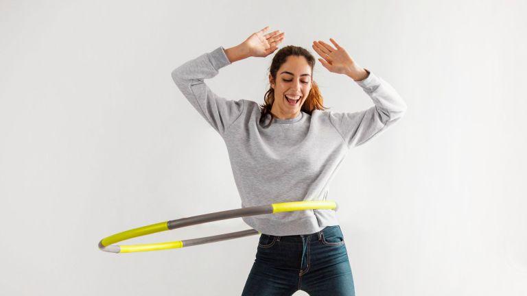 Kobieta w dresie ćwiczy z obciążonym hula hop