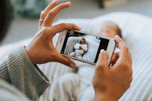 Matka robi smartfonem zdjęcie swojego nowonarodzonego dziecka