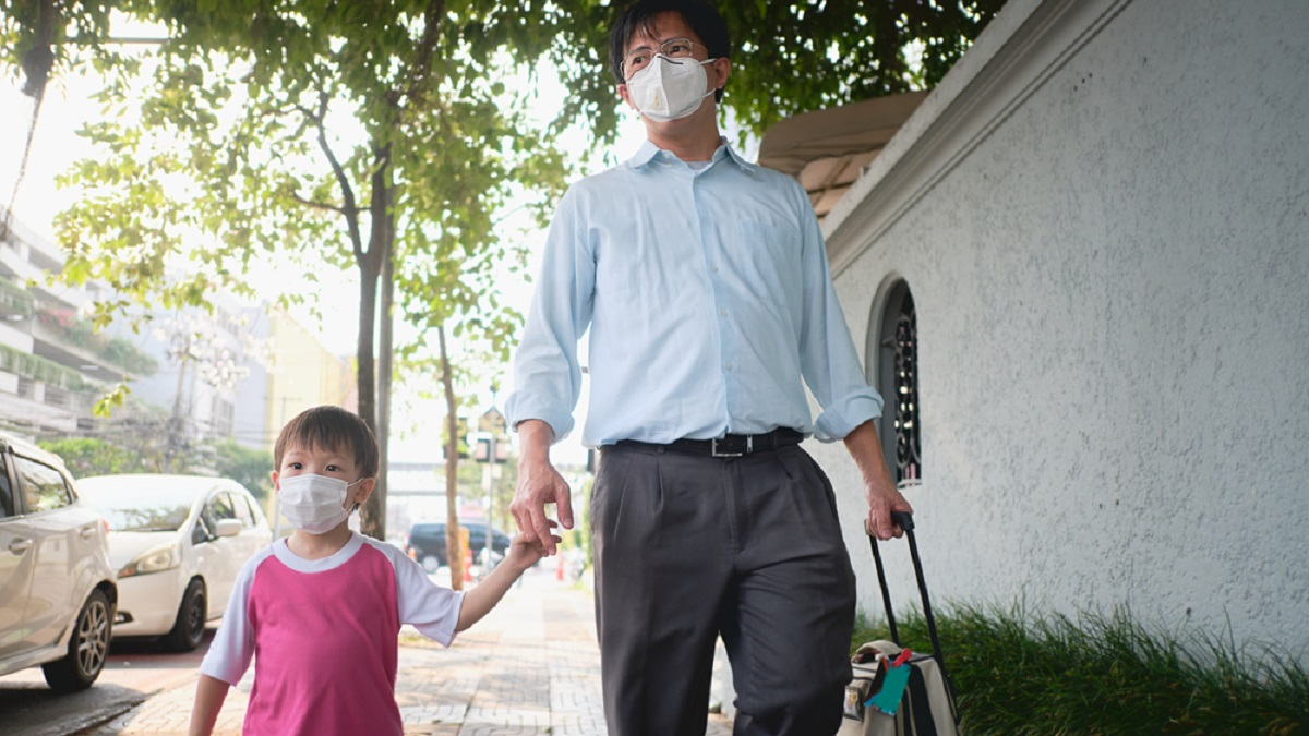 Father and child walking on street holding hands wearing face masks