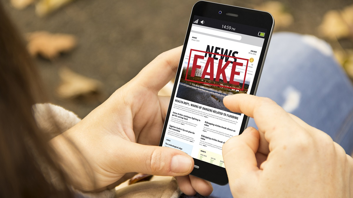"Person holding smart phone with words ""fake news"" on the screen"