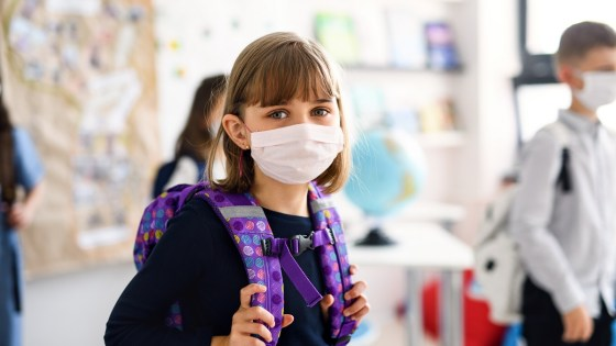 Young girl in classroom wearing facemask
