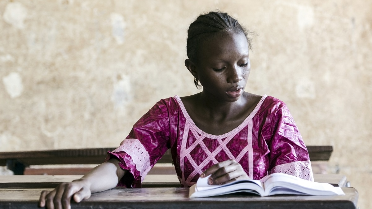 Young African girl sitting at a desk in a classroom reading a book
