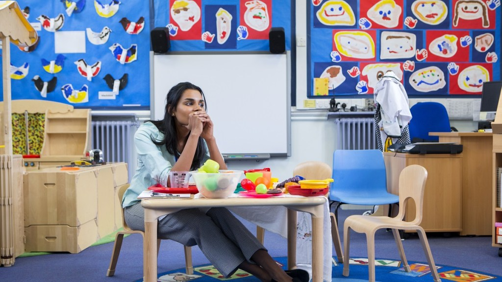 Female teacher in classroom sitting at table looking stressed
