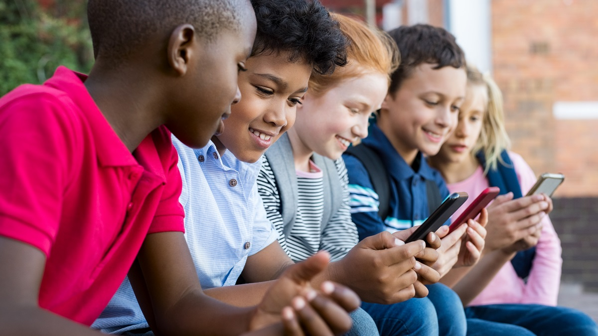Group of primary school children sitting in the school yard playing on their phones