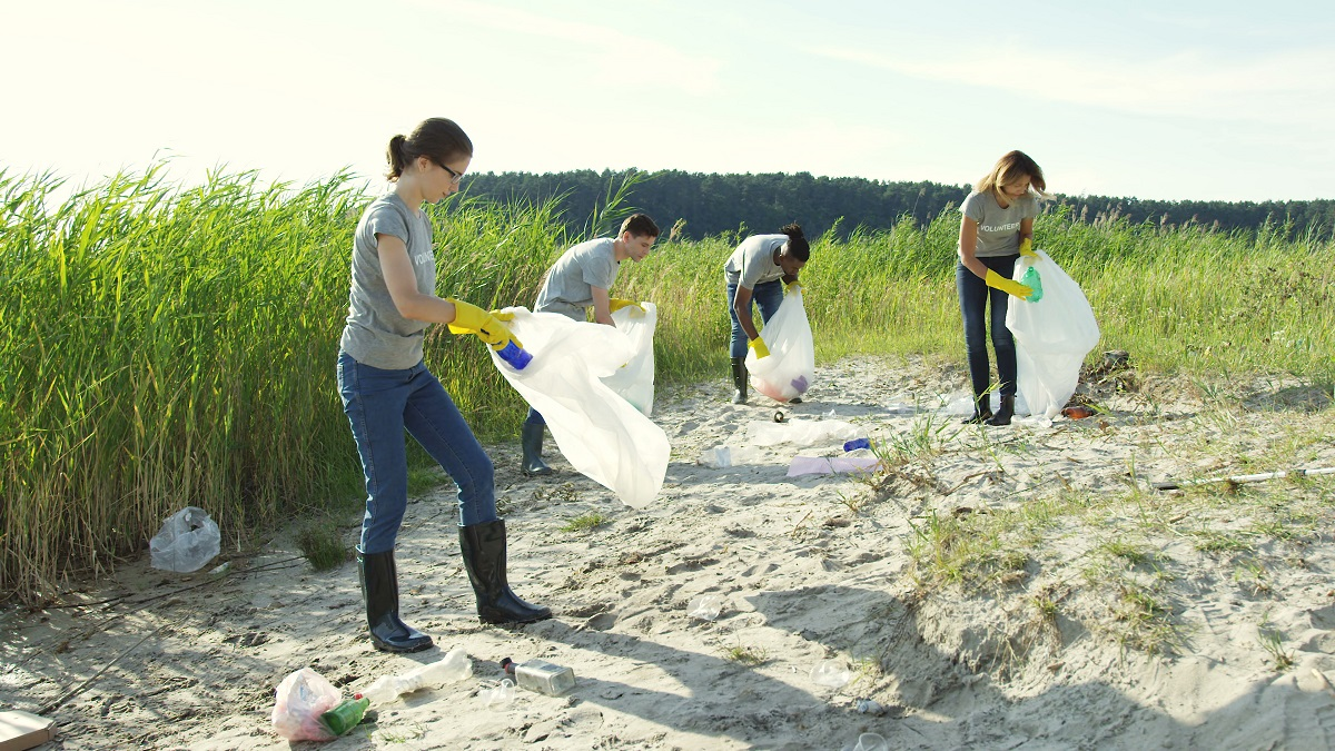 Teenagers picking up trash from a beach