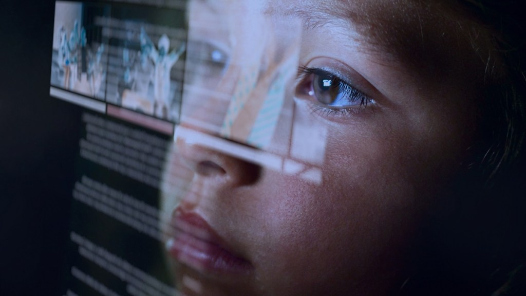 Young child staring at screen, face lit up by the screen