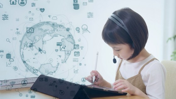 Young girl wearing computer headset plays on a tablet device - graphic world map hovering above
