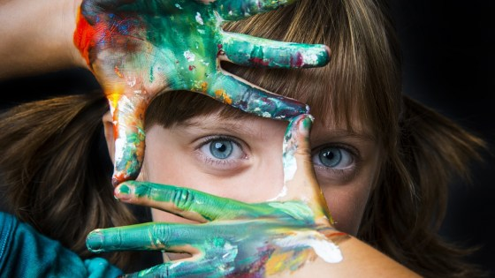Young girl holding her fingers in the shape of a square in front of her face and looking through them with one eye. Her hands are covered in paint.