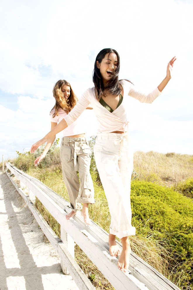 Young Women Smiling Walking on a Railing --- Image by © Royalty-Free/Corbis