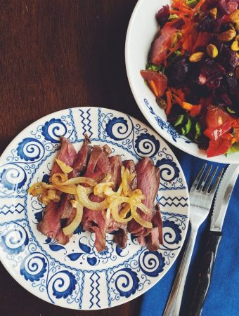 Seared Beef Heart garnished with sauteed onions and garlic served with a salad