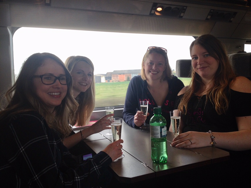 Group of girls drink prosecco while travelling by Eurostar train to Brussels
