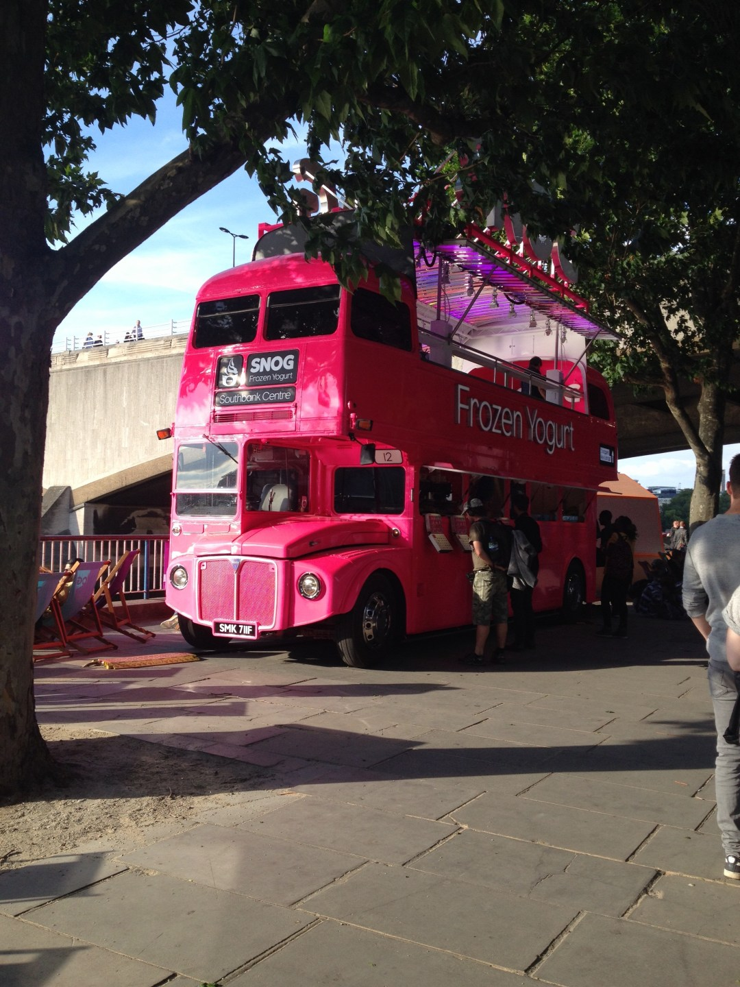 Pink double decker bus selling frozen yogurt on London's southbank
