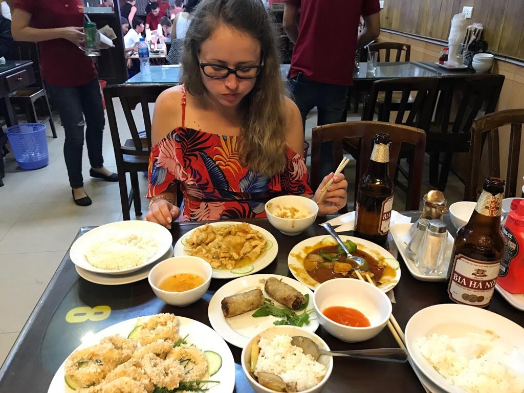 Girl tries selection of Vietnamese dishes at Hanoi restaurant New Day