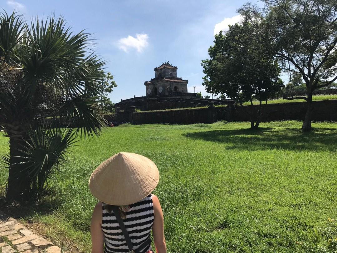 Girl in non la looking at ancient ruin in Hue
