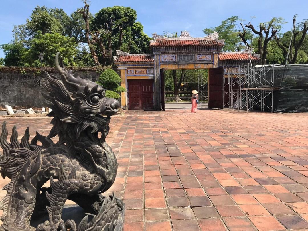 Dragon statue and girl in non-la in Hue Imperial City