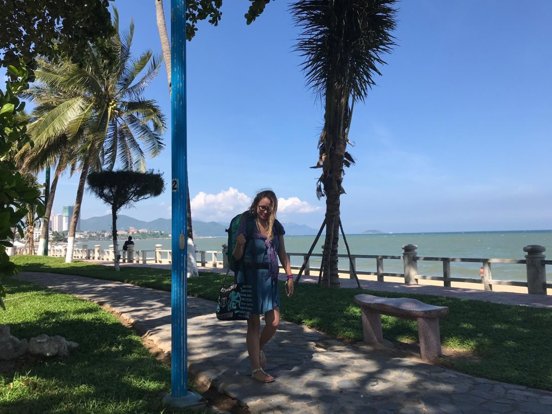 Girl with backpack on seafront in Nha Trang