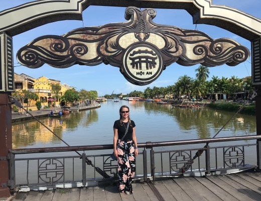 girl posing on bridge over Thu Bồn River in Hoi An, Central Vietnam wearing tshirt and loose cotton trousers