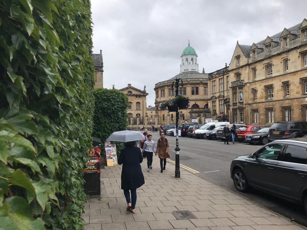 Girl walks through streets near Oxford University carrying an umbrella