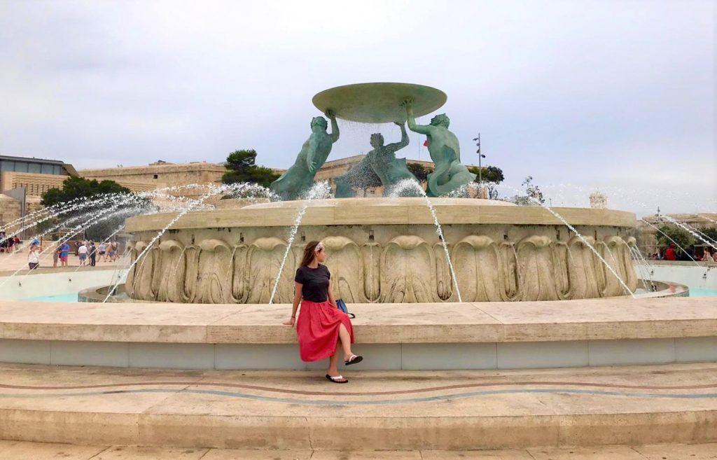 Girl sits on Triton Fountain in Valletta Malta