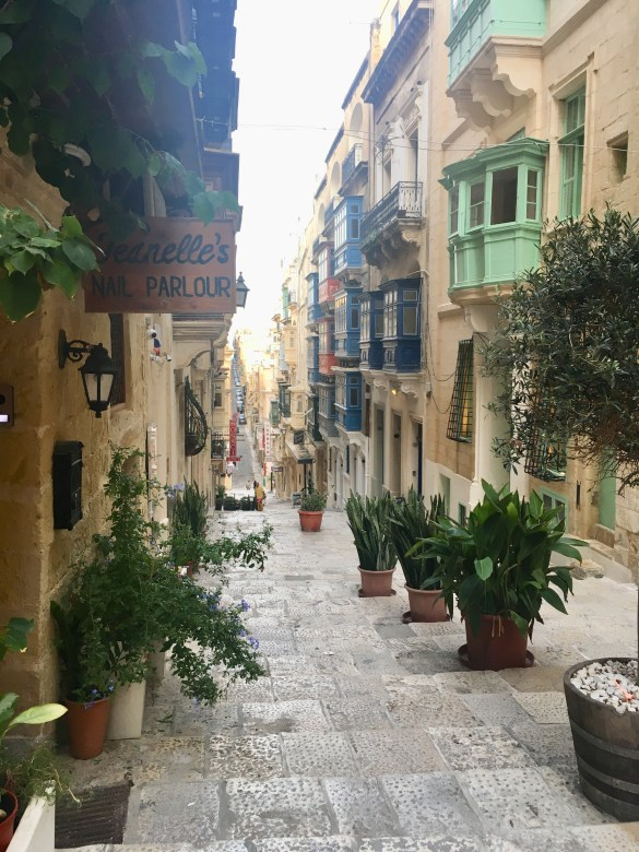 A street in Valletta Malta lined with plants and colourful balconies